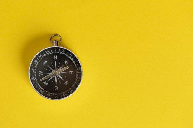 Photo d'une boussole sur un fond jaune