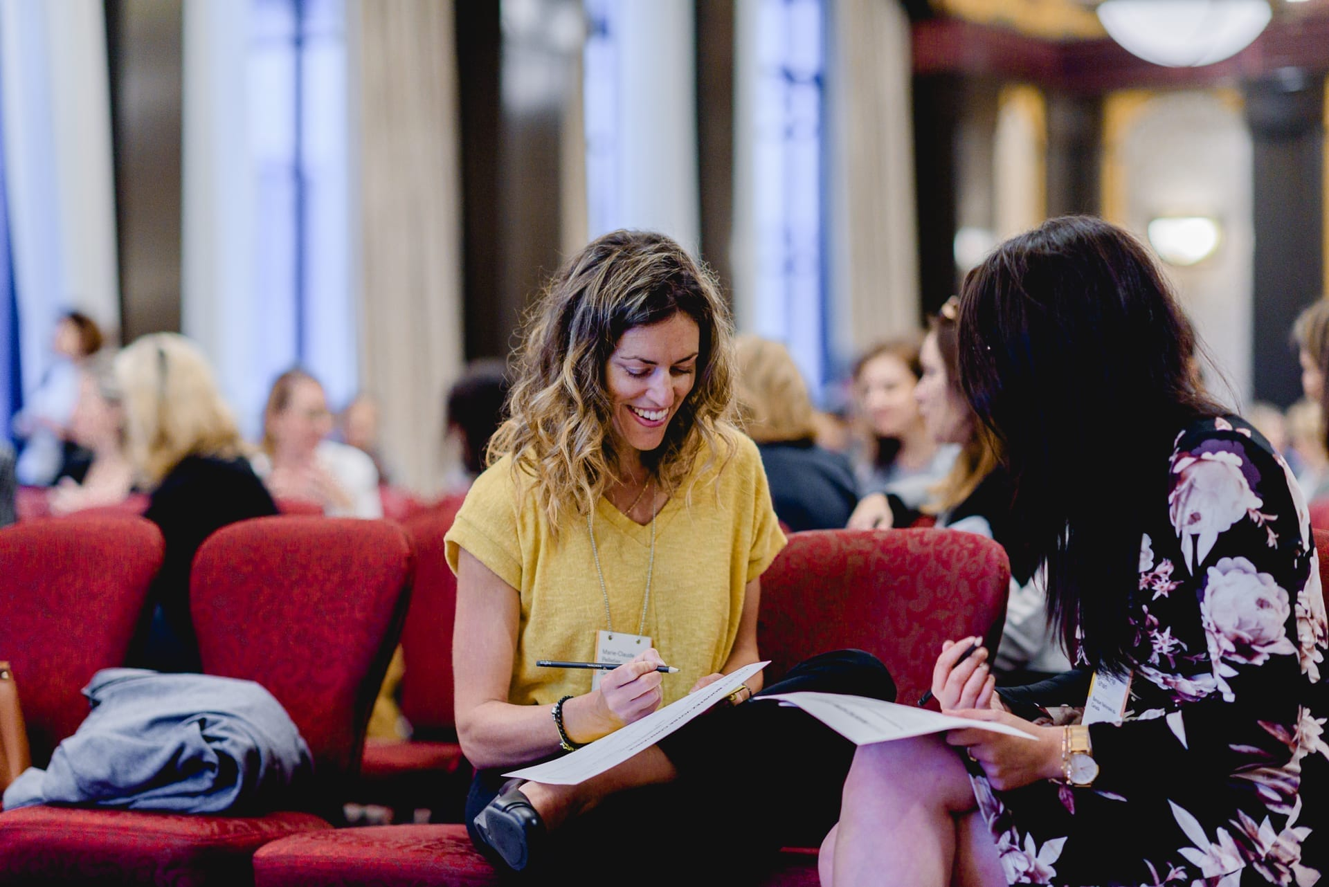 Femmes assises face à face sur des fauteuils rouges alignés et qui prennent des notes lors d'un atelier L'effet A.