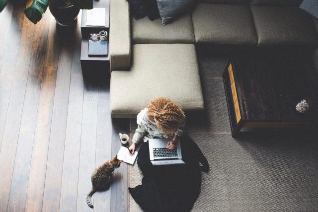 Photo d'une femme assise dans son salon, sur son ordnateur, prenant des notes