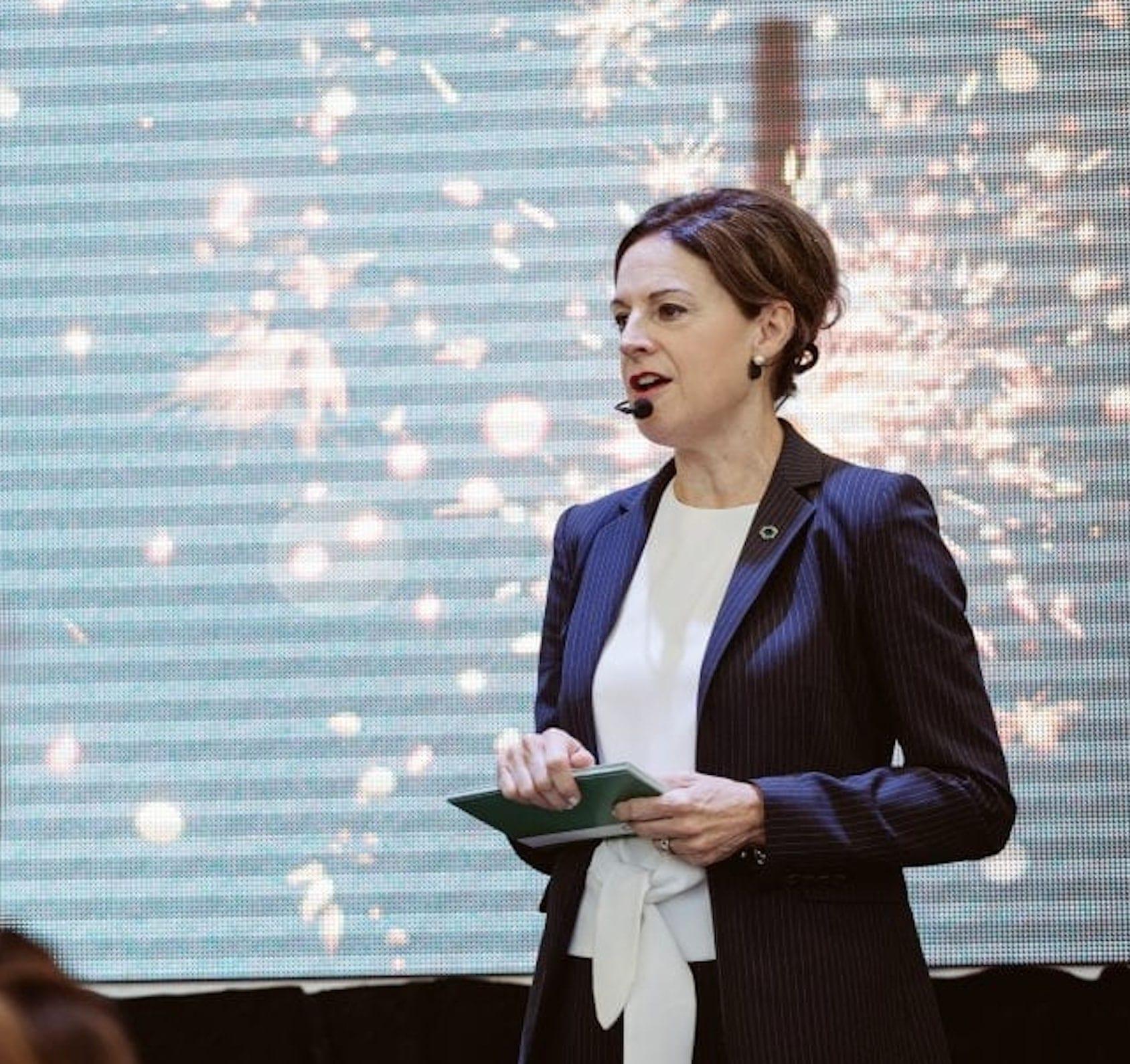 Femme parlant devant un public avec un micro